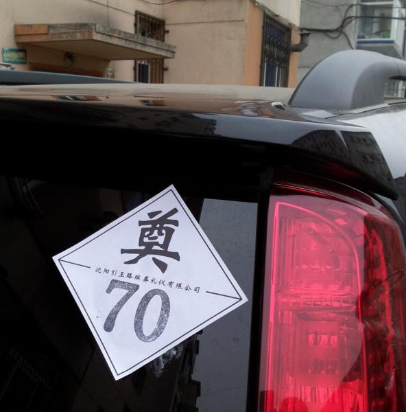 奠 (dian4, 'a libation to the dead'), and 70 denotes the deceased's age -- the text bisecting the sticker is the name of the company that printed it, seriously.