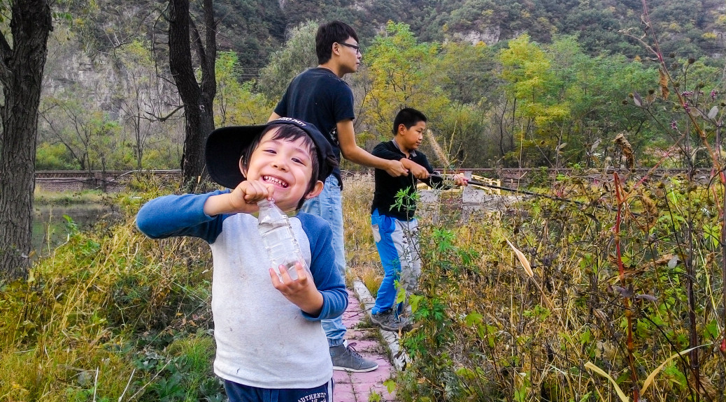 Teach a man to fish, feed him for a lifetime. Teach a child to fish, thrill him for an afternoon! Catching your own fish is true happiness! In the background Uncle Dandan helps ErWan try and get one too.